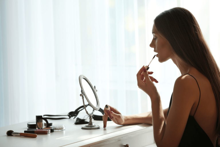 Young woman adding lipgloss while sat at a vanity unit