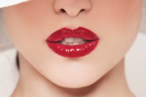 Young woman with very red lips after lip blush treatment