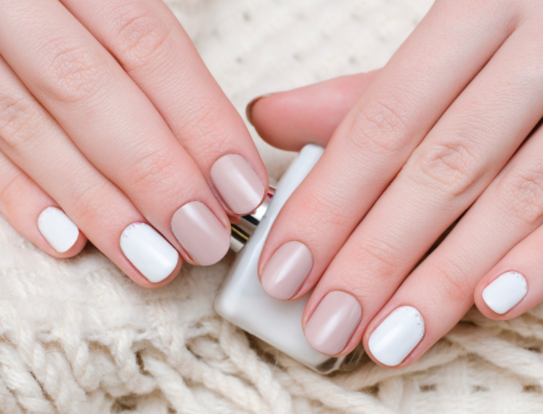 Manicured female hands holding a bottle of nail polish